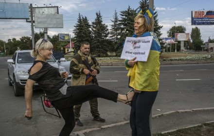 An alleged spy for Ukrainian troops, who was captured by the Donetsk People?s Republic, stands wrapped in a Ukrainian flag as a passerby kicks her in Donetsk, Ukraine, Aug. 25, 2014. Foreign Minister Sergey Lavrov said Russia hoped to send a second convoy into east Ukraine this week, despite the widespread condemnation prompted by the last one. (Mauricio Lima/The New York Times)