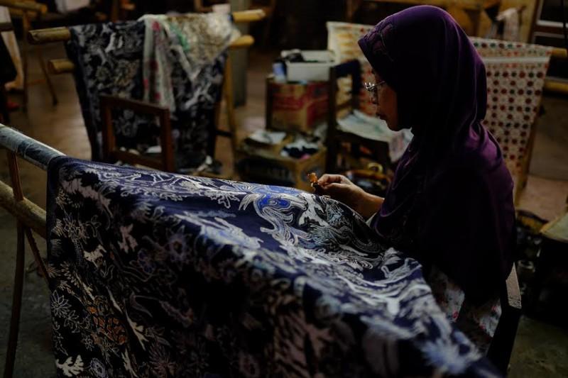 Старенька мусульманка малює традиційні яванські символи, притаманні яванському містицизму